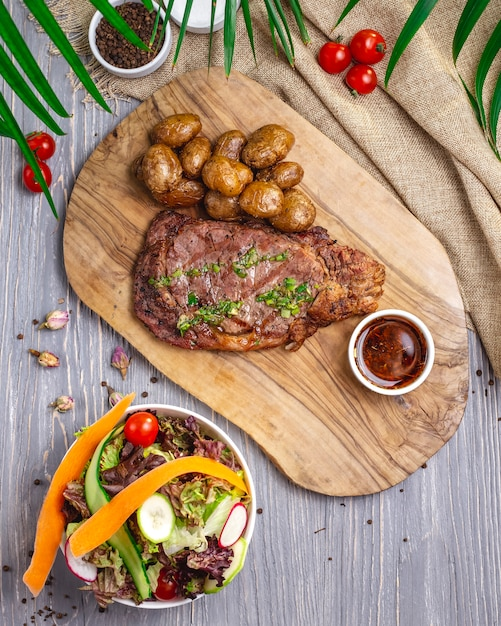Top view steak with potatoes and sauce on the board with salad and vegetables Free Photo