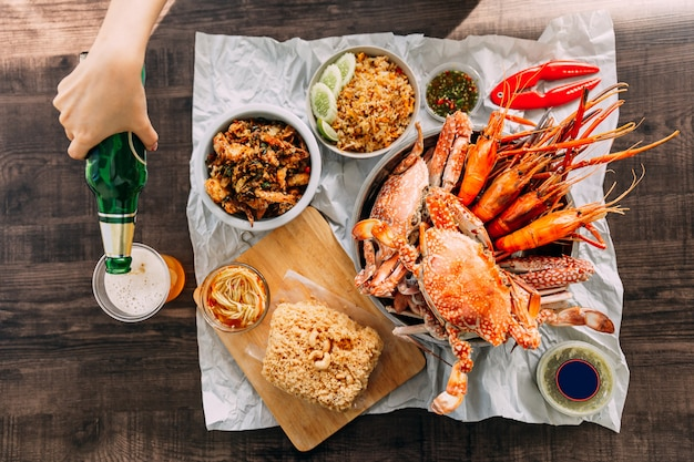 Top view of steamed giant mud crabs, grilled prawns (shrimps), crab fried rice, pepper and garlic soft-shell crab, crispy catfish, mango salad and thai spicy seafood sauce. served with beer. Premium Photo