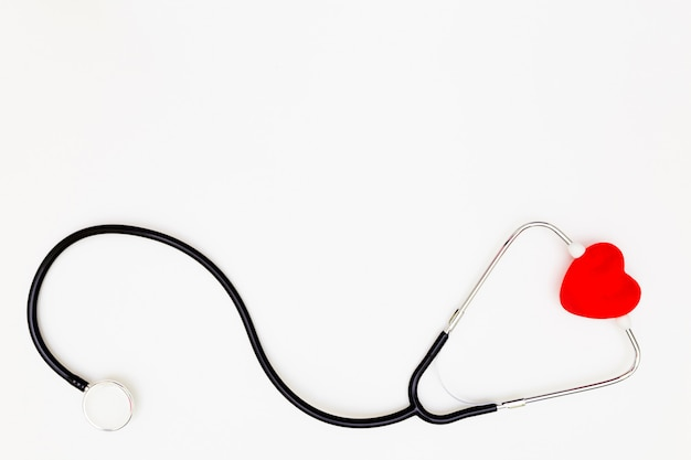 Top view of stethoscope and red heart on white background Premium Photo