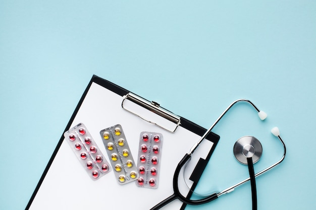 Top view stethoscope with pills on notepad Free Photo