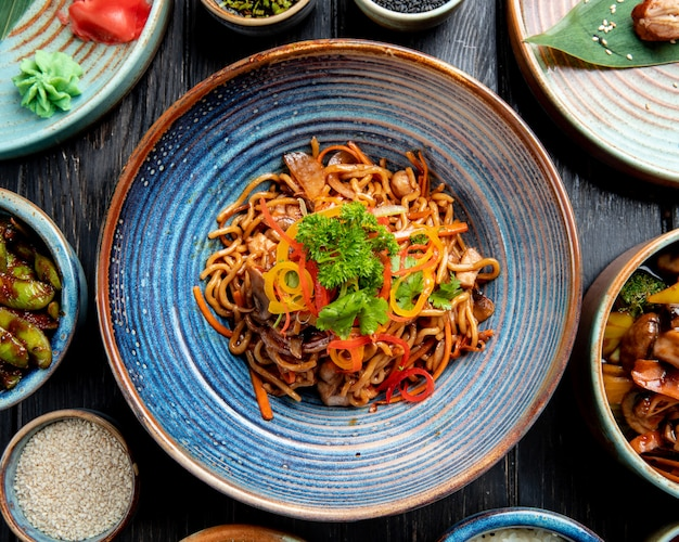 Top view of stir fried noodles with vegetables and shrimps in a plate on wooden table Free Photo