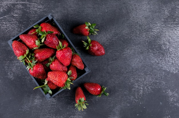 Top view strawberries in a box and others around Free Photo