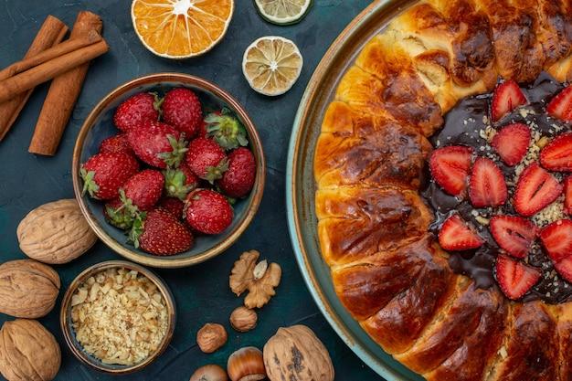 Vista dall'alto della torta di fragole con noci e bastoncini di cannella Foto Gratuite