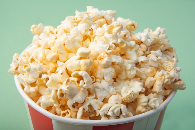 Top view of striped paper cup with popcorn. snack for a movie. close-up. Premium Photo