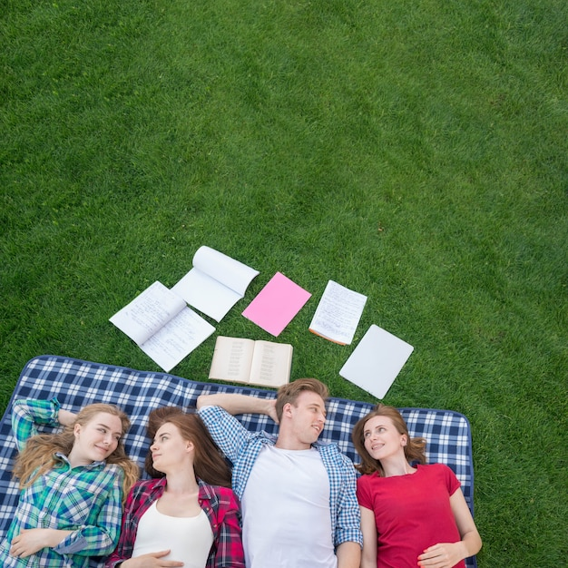 Top view of students lying on picnic blanket Free Photo