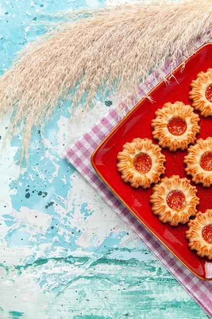 青い背景の上の赤いプレート内の上面のシュガークッキー 無料写真