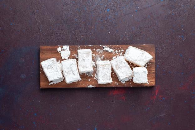 Vista dall'alto del torrone di caramelle in polvere di zucchero sulla superficie scura Foto Gratuite