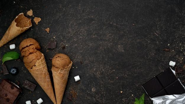 Top view of summer dessert with chocolate flavour ice-cream cones  on dark table Premium Photo