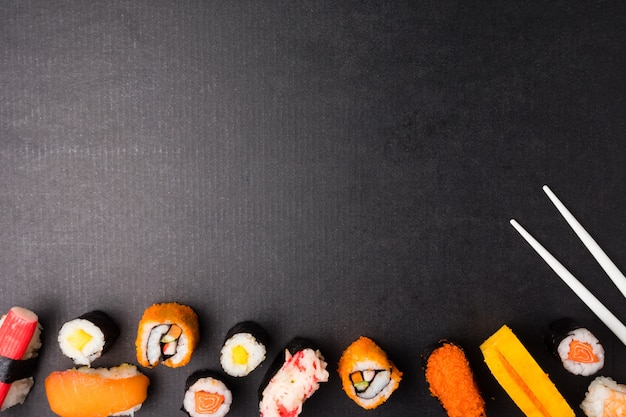 Top view of sushi set and chopsticks on black background, japanese food. Premium Photo