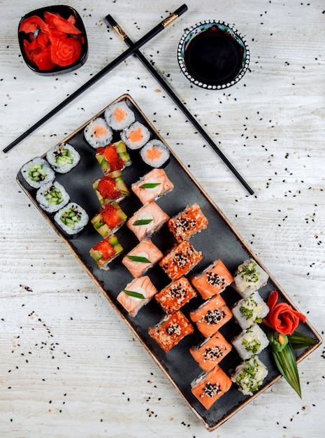 Top view of sushi set served with wasabi, ginger, and soy sauce Free Photo