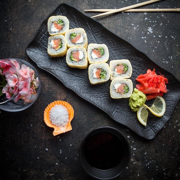 暗い皿に生姜の漬物とわさびと醤油と箸でトップビュー寿司セット 無料写真