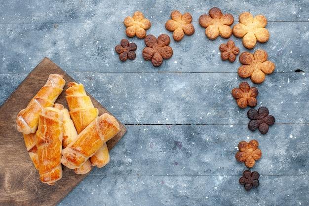 灰色の背景にクッキーと甘い腕輪の上面図甘い焼きペストリーケーキシュガービスケット 無料写真