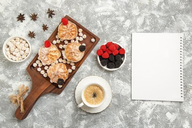 ライトホワイトの机の上にキャンディーとコーヒーのトップビューの甘いケーキ 無料写真