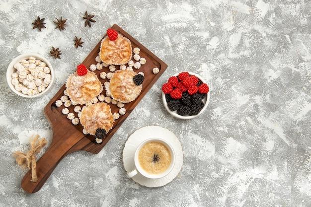 Вид сверху сладкие пирожные с конфетами и чашкой кофе на белом фоне Бесплатные Фотографии