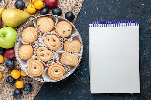 ダークブルーのデスクにさまざまな新鮮なフルーツのメモ帳と一緒にトップビューの甘いクッキーフルーツクッキービスケット甘い新鮮な 無料写真