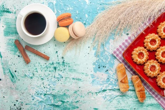 밝은 파란색 배경에 베이글 마카롱과 차 한잔과 함께 상위 뷰 달콤한 쿠키 무료 사진