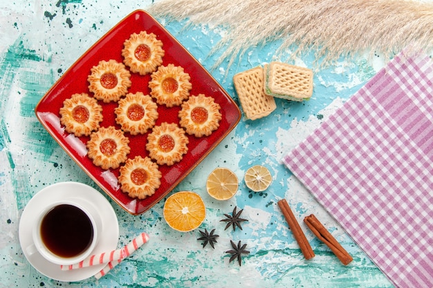 オレンジ色のジャムと水色の背景にお茶のトップビュー甘いクッキー 無料写真