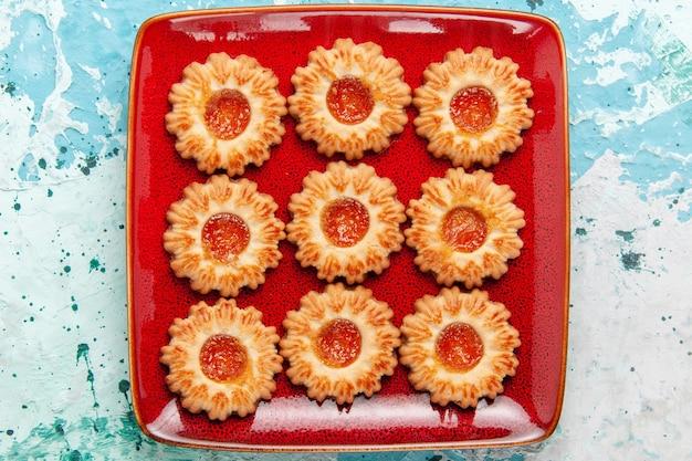 Vista dall'alto biscotti dolci con marmellata di arance all'interno del piatto rosso su sfondo blu Foto Gratuite