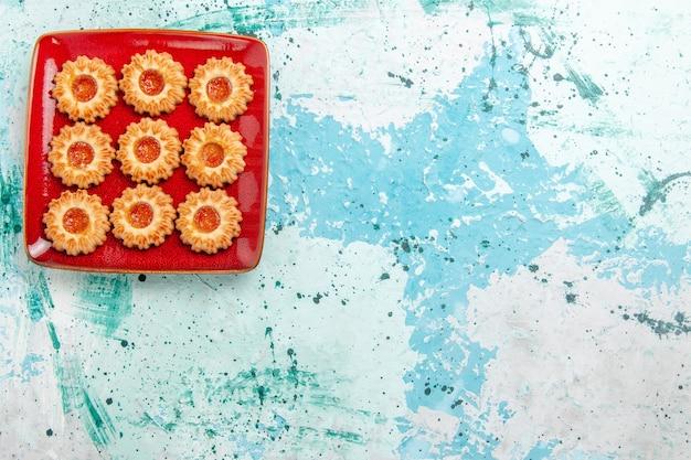 파란색 배경에 빨간 접시 안에 오렌지 잼 상위 뷰 달콤한 쿠키 무료 사진