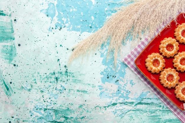 青い背景にオレンジ色のジャムとトップビューの甘いクッキー 無料写真