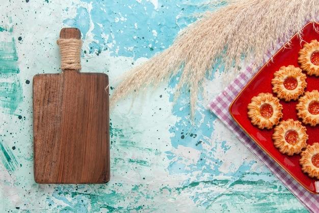 水色の背景にオレンジ色のジャムと甘いクッキーの上面図 無料写真