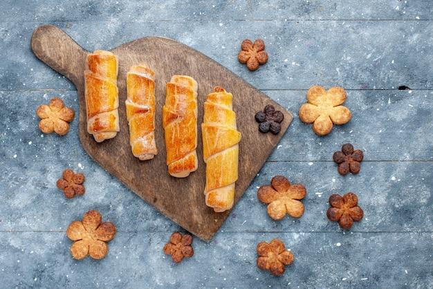 灰色の木製の背景にクッキーと一緒に詰め物と甘いおいしい腕輪の上面図甘い砂糖焼きペストリー 無料写真