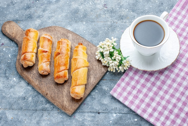 灰色の木製のテーブルにコーヒーの白い花のカップと一緒に充填された上面図甘いおいしい腕輪甘い砂糖焼きペストリークッキービスケット 無料写真