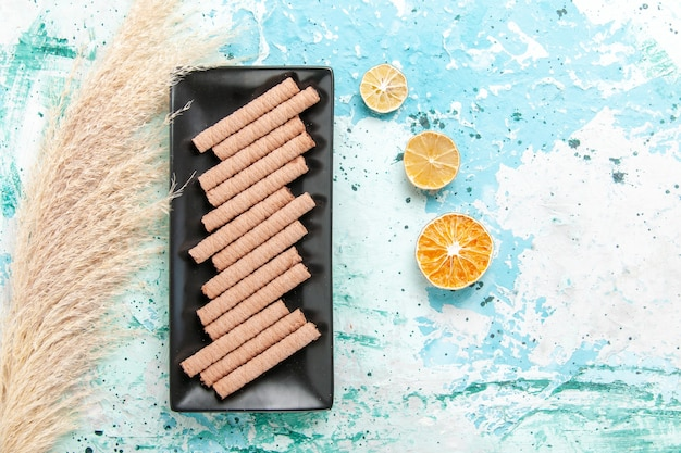 青い背景の上の黒いケーキパンの中の甘い長いクッキーの上面図 無料写真