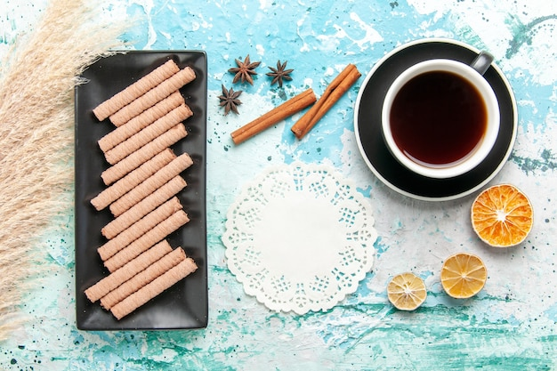 Vista dall'alto dolci biscotti lunghi con una tazza di tè e cannella su sfondo blu Foto Gratuite