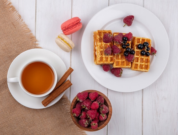 Top view sweet waffles on a plate with a cup of tea cinnamon and raspberries with macaroons on a white table Free Photo