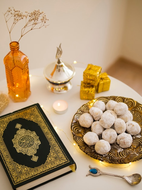 Top view table arrangement with quran, pastries and tea Free Photo