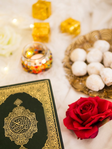 Top view table arrangement with quran, roses and pastries Free Photo