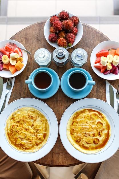 Top view, table setting, balinese tropical breakfast of fruit, coffee, scrambled eggs and banana pancake Premium Photo