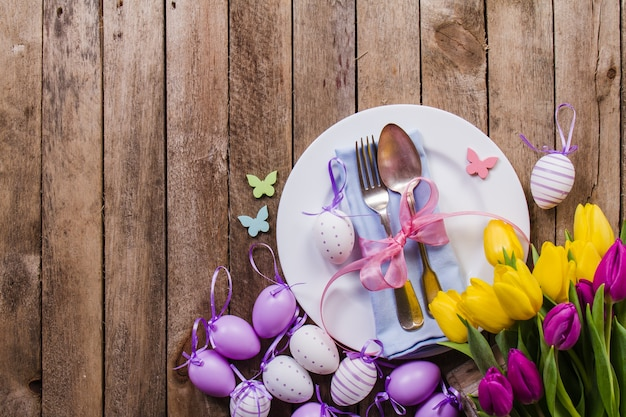Top view of table with easter eggs and decorative flowers Free Photo
