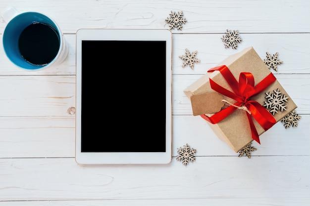 トップビュータブレット、カップコーヒー、クリスマスや新年の白い木の背景に雪片とギフトボックス。 Premium写真
