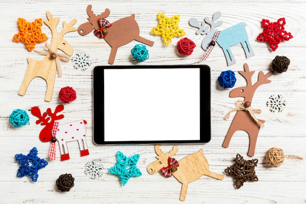 Top view of tablet on holiday wooden table. new year decorations and toys. christmas concept Premium Photo
