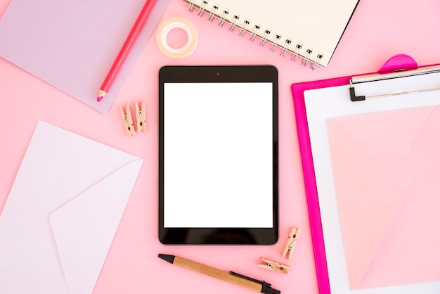 Top view tablet with pink stationery Free Photo