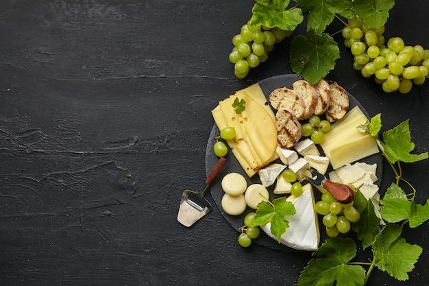 Vista dall'alto del gustoso piatto di formaggi con frutta, uva su un piatto da cucina cerchio su pietra nera Foto Gratuite