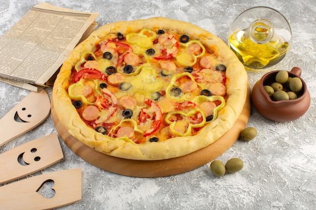 Vista dall'alto gustosa pizza di formaggio con olive nere salsicce e pomodori rossi insieme a olio e olive sullo sfondo grigio fast-food pasta italiana pasto cuocere Foto Gratuite