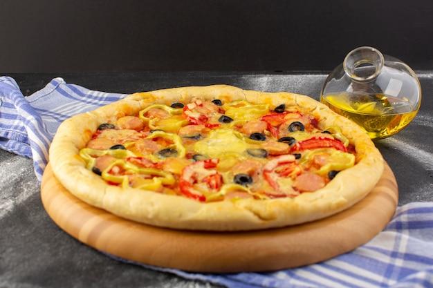 Vista dall'alto gustosa pizza di formaggio con pomodori rossi olive nere e salsicce con olio su sfondo scuro pasto fast food pasta italiana Foto Gratuite