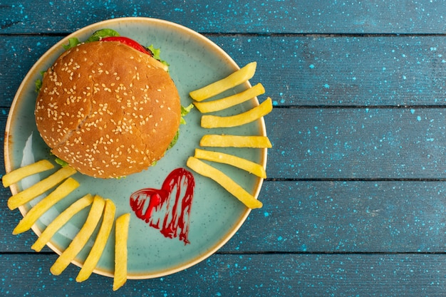 Top view of tasty chicken sandwich with green salad and vegetables inside plate with french fries on the wooden blue surface Free Photo