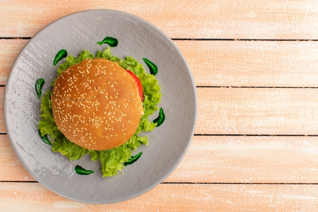 Top view of tasty chicken sandwich with green salad and vegetables inside plate on the wooden rustic cream surface Free Photo