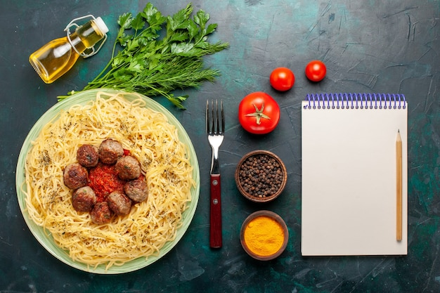Top view tasty italian pasta with meatballs and different seasonings on the dark blue background Free Photo