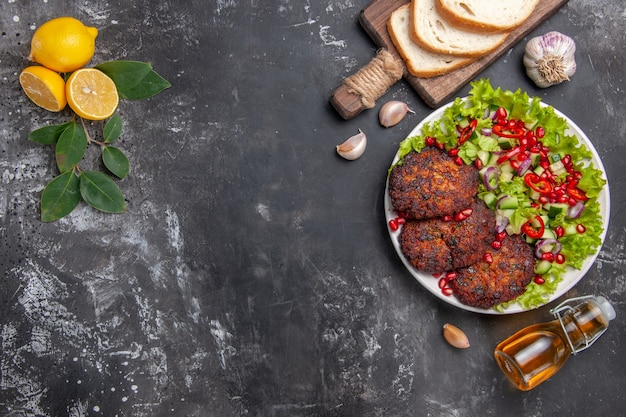 Top view tasty meat cutlets with salad and bread on the grey background dish photo food meal Free Photo