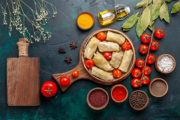 Top view tasty meat meal rolled inside cabbage with seasonings oil and fresh tomatoes on dark-blue desk Free Photo