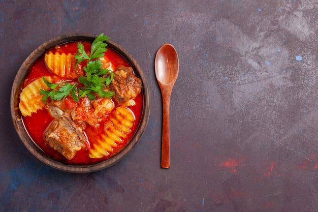 Vista dall'alto gustosa zuppa di ragù di carne con verdure e patate a fette sul nero Foto Gratuite