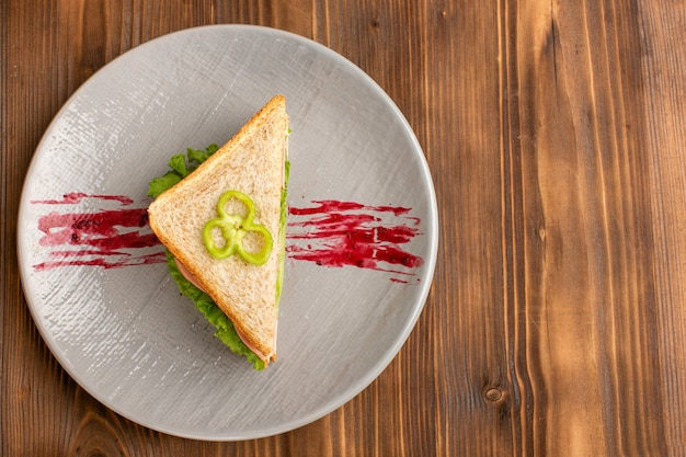 Top view of tasty sandwich inside plate on the wooden desk Free Photo