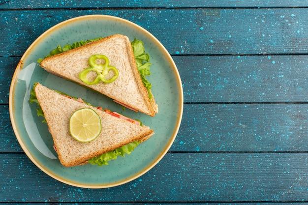 Vista dall'alto di gustosi panini con insalata verde e prosciutto all'interno della piastra Foto Gratuite