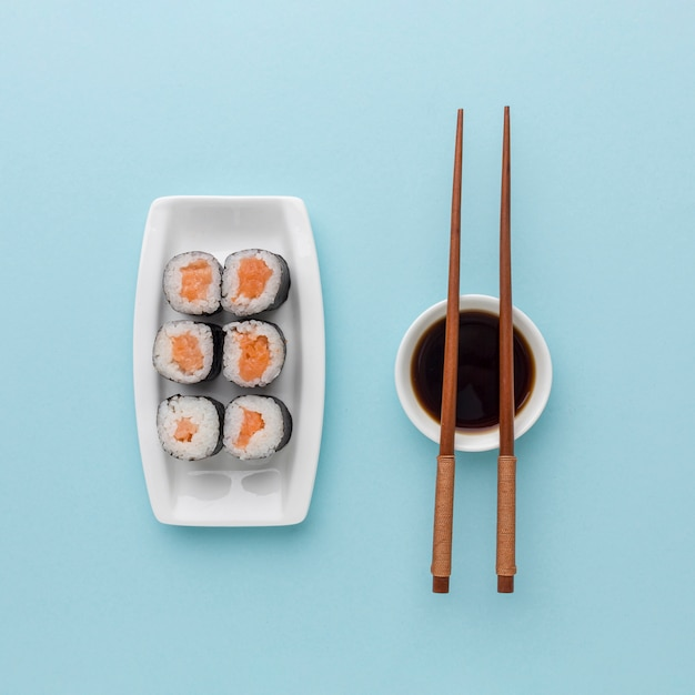 Top view tasty sushi rolls with soy sauce and chopsticks Free Photo