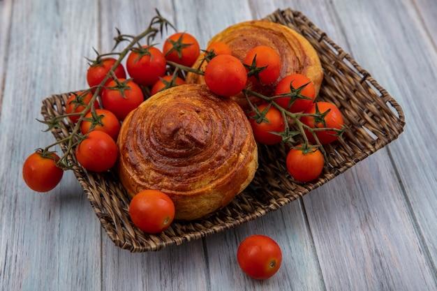 Vista dall'alto della gustosa pasticceria azerbaigiana tradizionale gogal su un vassoio di vimini con pomodori a grappolo su un fondo di legno grigio Foto Gratuite
